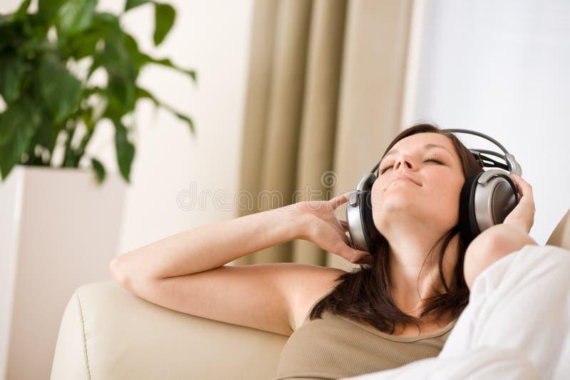 耳机听微笑的音乐妇女 免版税图库摄影