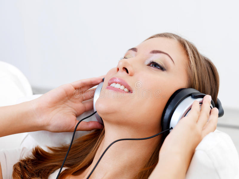 耳机听的音乐妇女 免版税库存图片