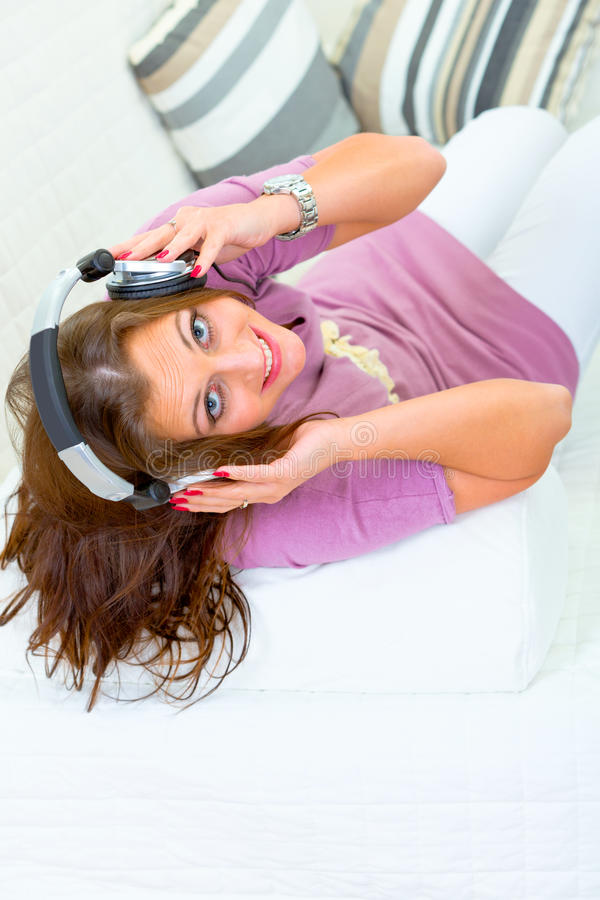 耳机听的音乐沙发妇女 库存照片