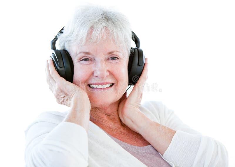 耳机听的音乐高级微笑的妇女 库存照片