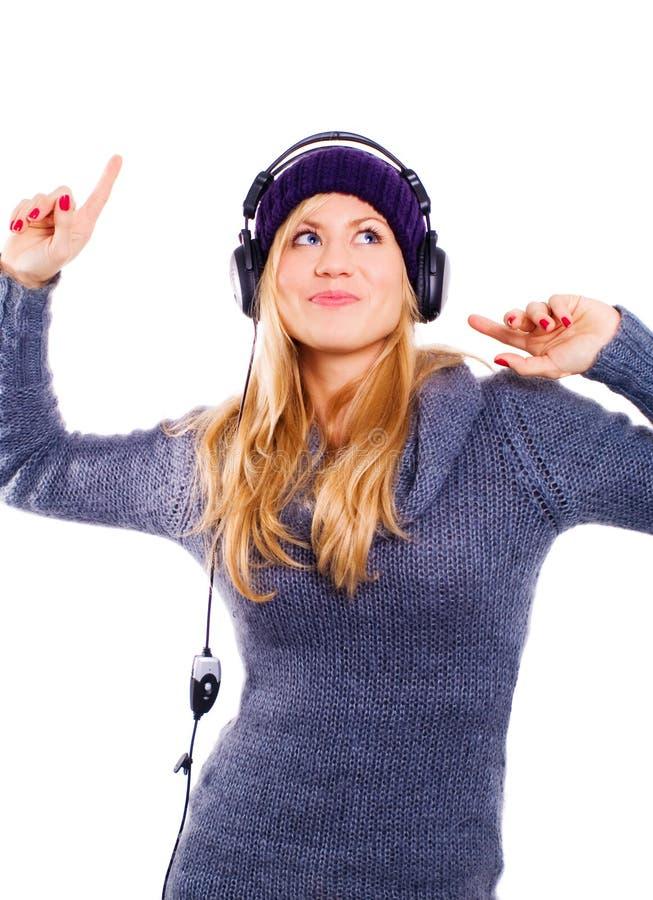 耳机听的musi微笑的妇女 免版税库存图片
