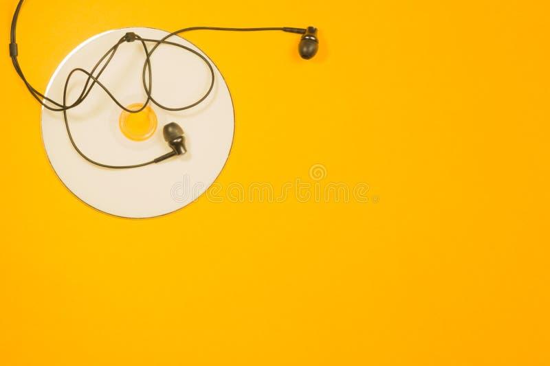 耳机和光盘在黄色背景 复制空间 免版税库存照片