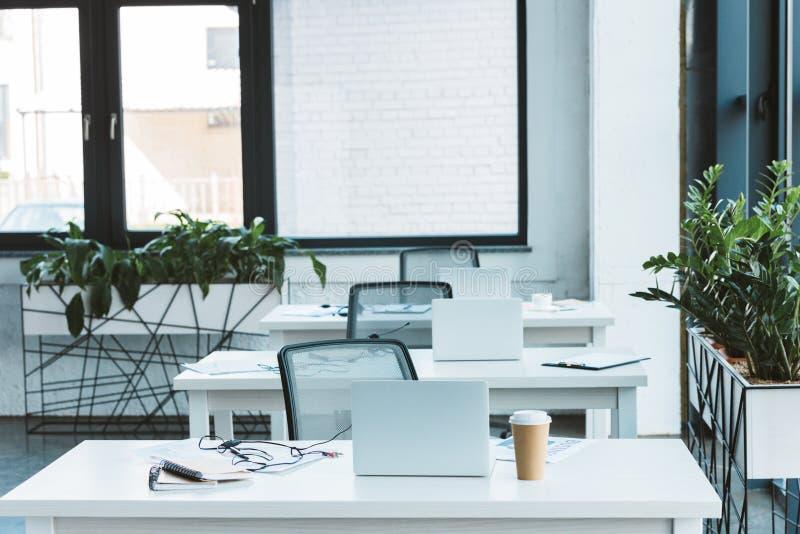 耳机和膝上型计算机在桌上在轻倒空 图库摄影