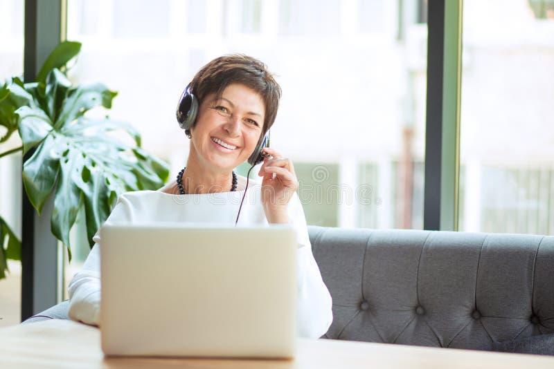 耳机和膝上型计算机的年迈的妇女在桌上 免版税库存图片