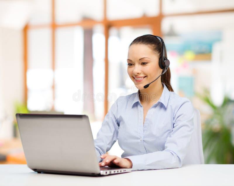 耳机工作的热线服务电话操作员在办公室 库存照片