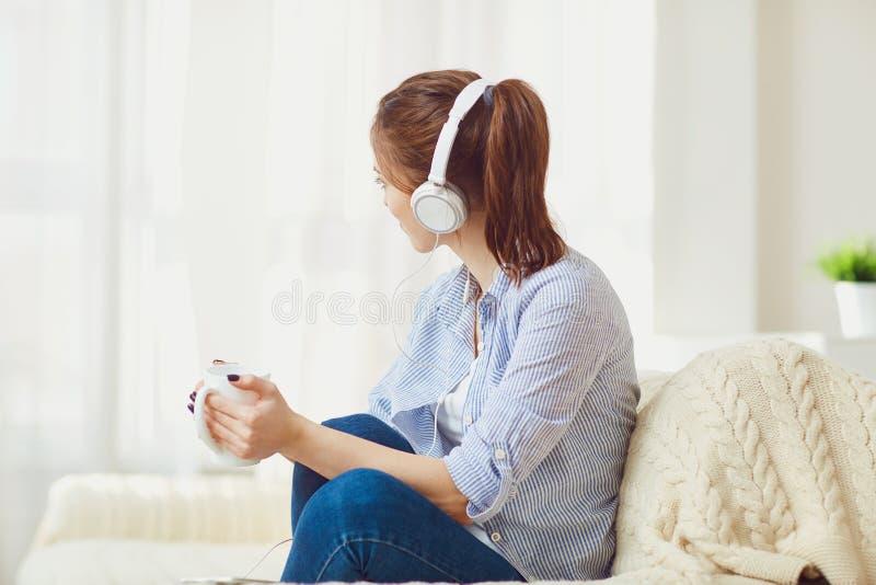 耳机的一个女孩听到看窗口的音乐 免版税库存照片