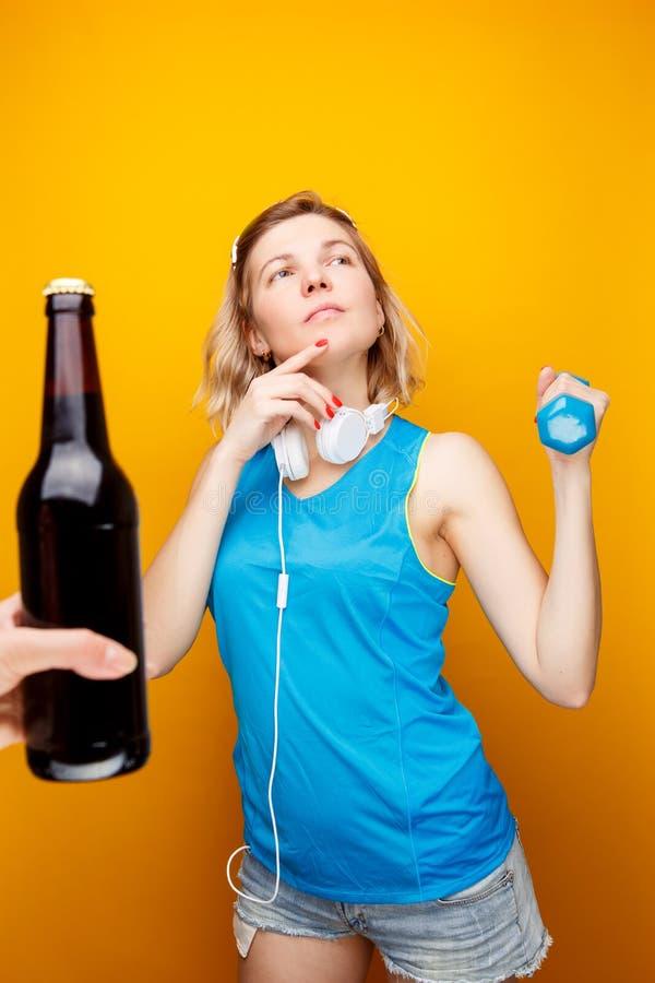耳机的体贴的运动女孩有哑铃的在手中在有瓶的手前面啤酒 库存图片