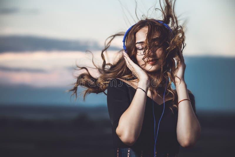 耳机的听到在自然的音乐的一个美丽的女孩的画象 库存照片
