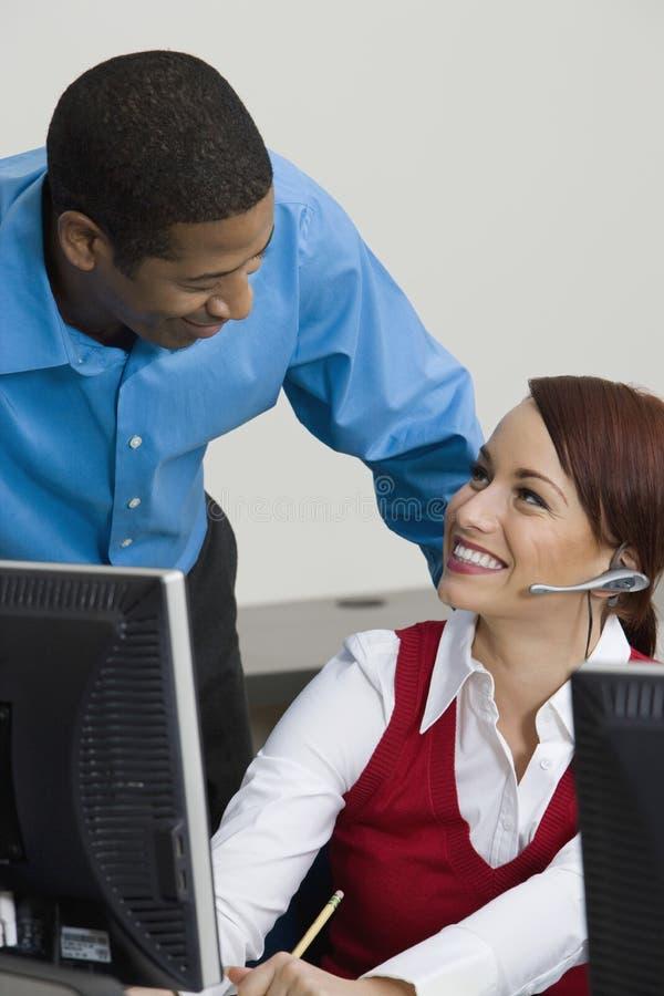 耳机的女实业家聊天与同事的 免版税库存图片