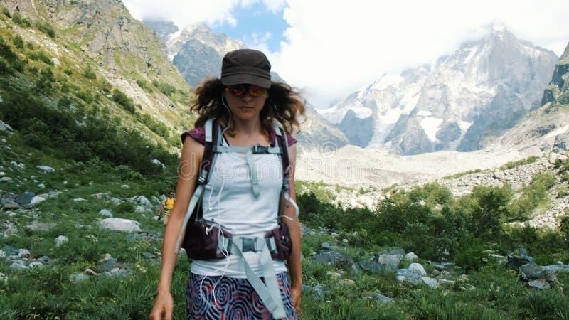 耳机的妇女游人与下降在一次远足的小山下与美好的风景 有一个背包的女孩在 库存照片