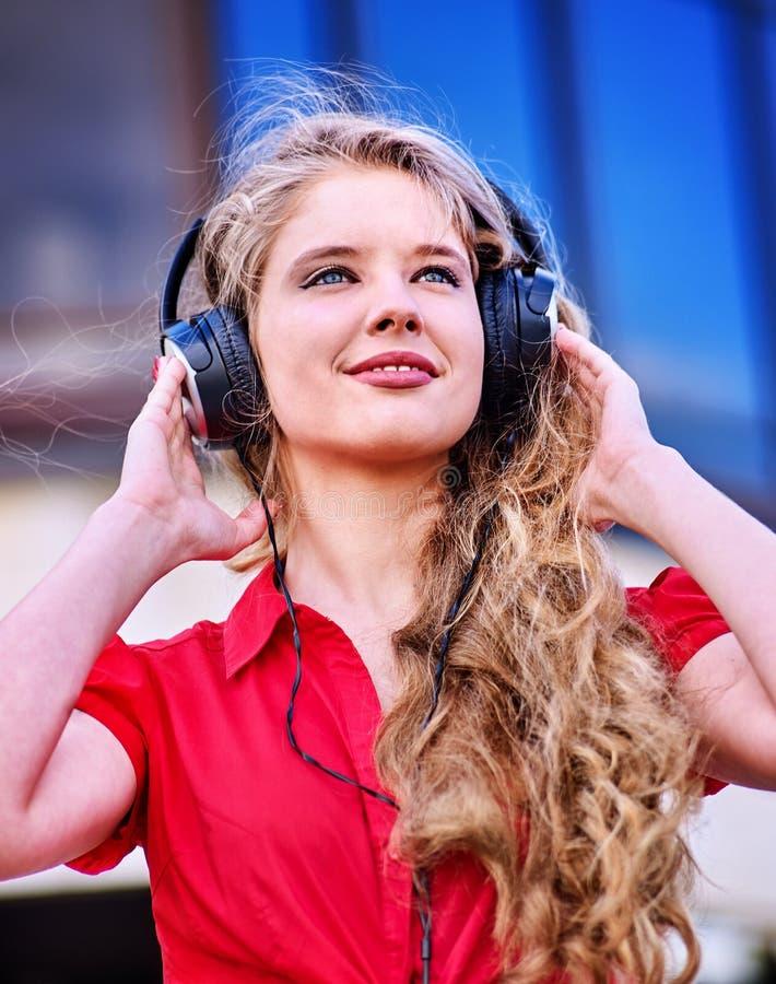 耳机的学生女孩听音乐 库存图片