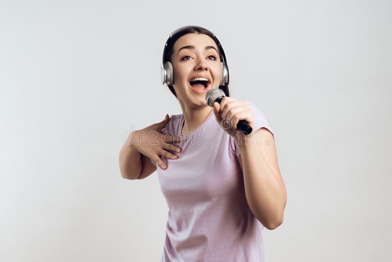 耳机的少女传神唱歌 库存图片