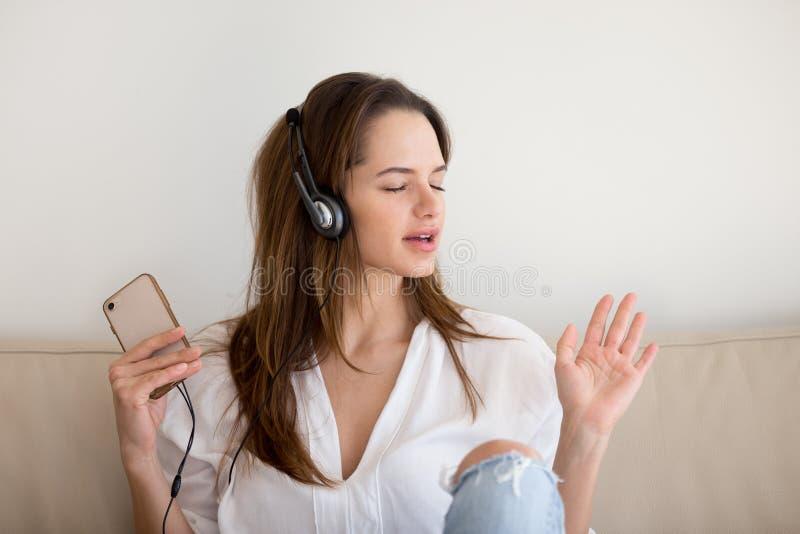 耳机的少妇听到音乐的使用智能手机ap 免版税库存照片