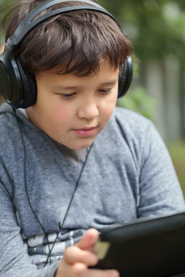 耳机的少年使用室外的垫 库存图片