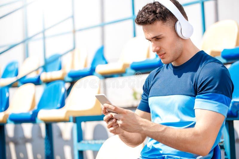 耳机的年轻人在坐的听的音乐浏览智能手机之外的体育场放松了 免版税库存照片