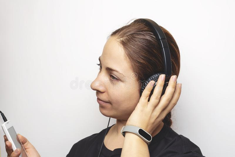 耳机的年轻白种人妇女在顶头听的音乐网上收音机或播客从流动智能手机 图库摄影