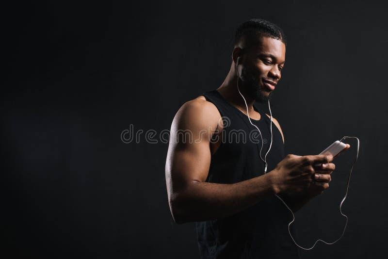 耳机的微笑的肌肉非裔美国人的人使用智能手机 库存图片
