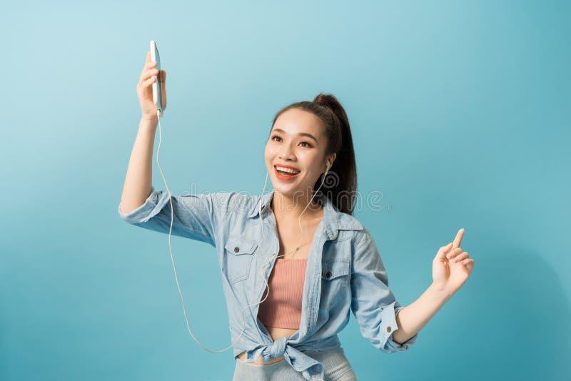 耳机的快乐的妇女听音乐和跳舞的被隔绝在蓝色背景 库存照片