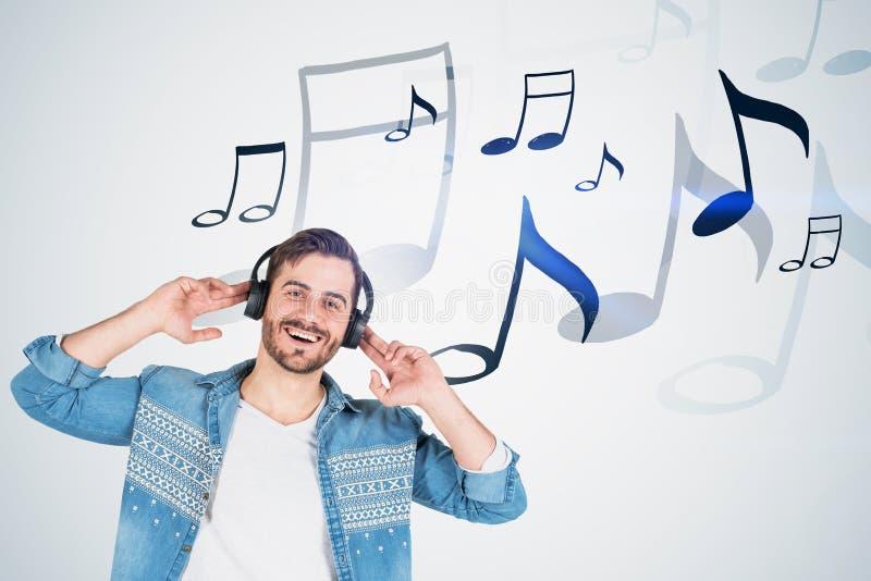 耳机的愉快的人,有笔记的白色墙壁 免版税库存照片