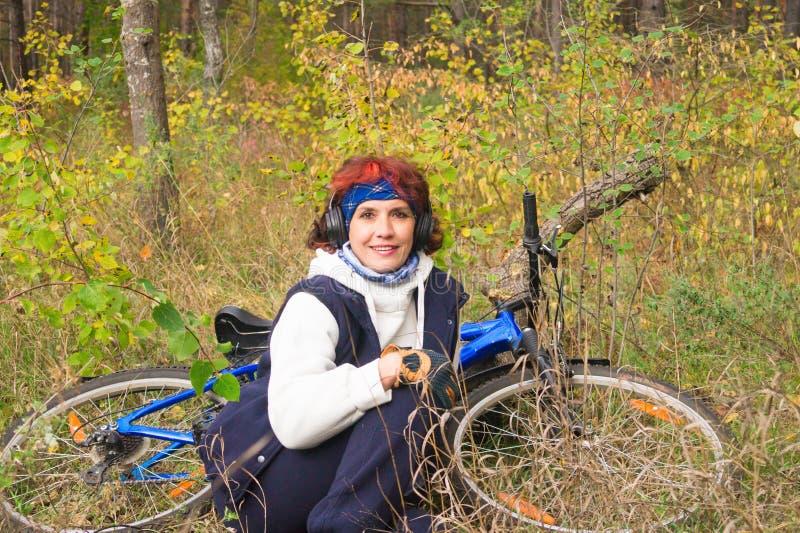耳机的欧洲可爱的妇女在的秋天森林里 免版税库存图片