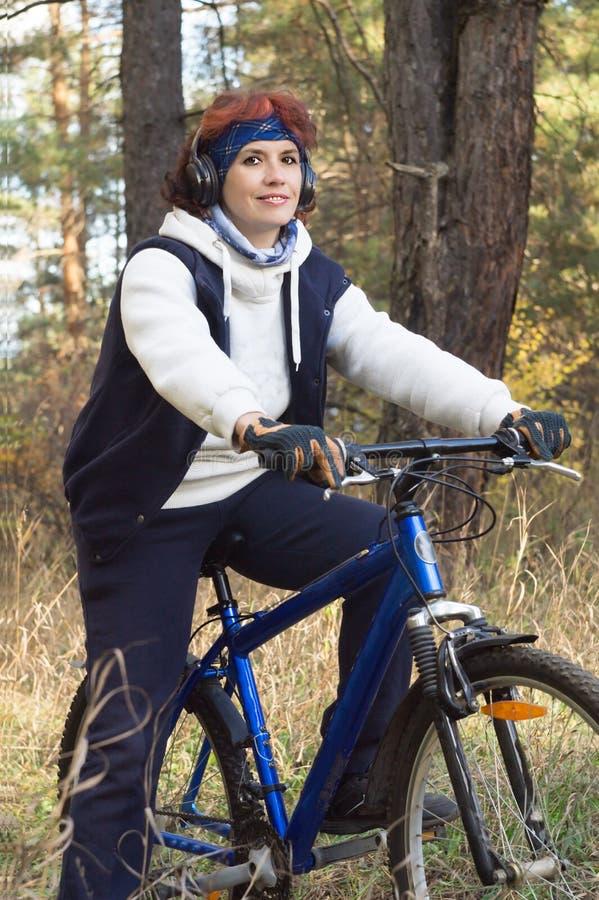 耳机的欧洲可爱的妇女在的秋天森林里 库存照片