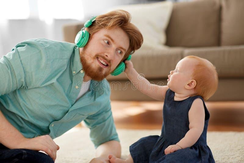 耳机的父亲有小女儿的在家 免版税图库摄影