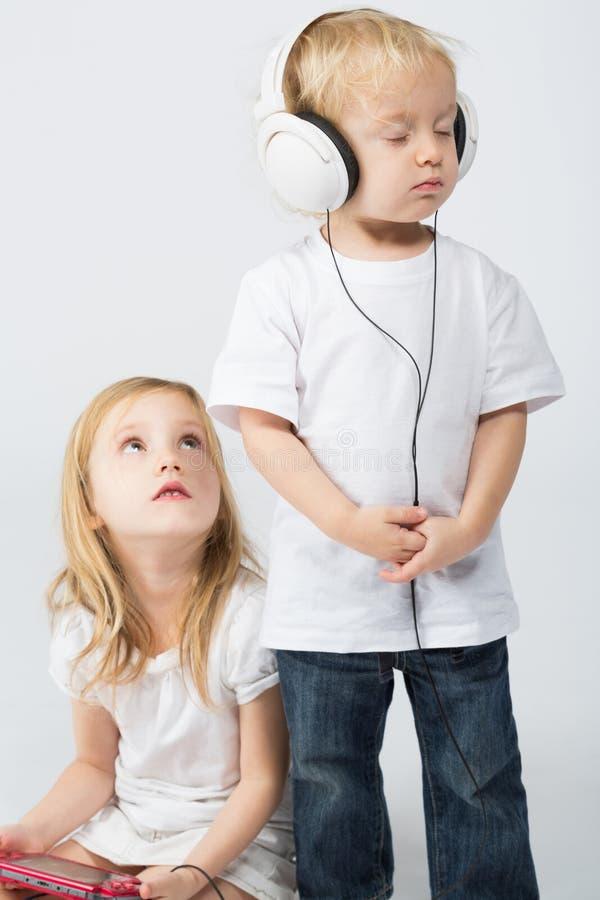 耳机的男孩有闭合的眼睛和女孩的 免版税库存图片