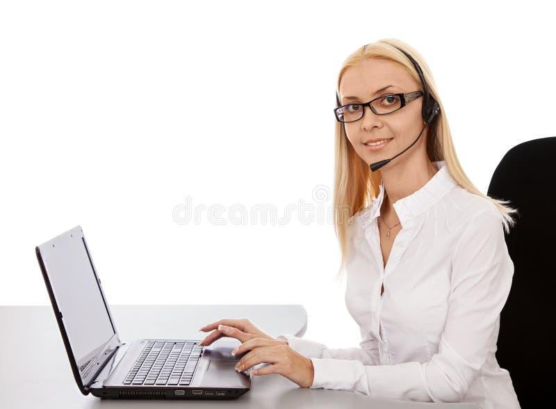 耳机的秘书美丽的女孩膝上型计算机的,微笑 库存照片