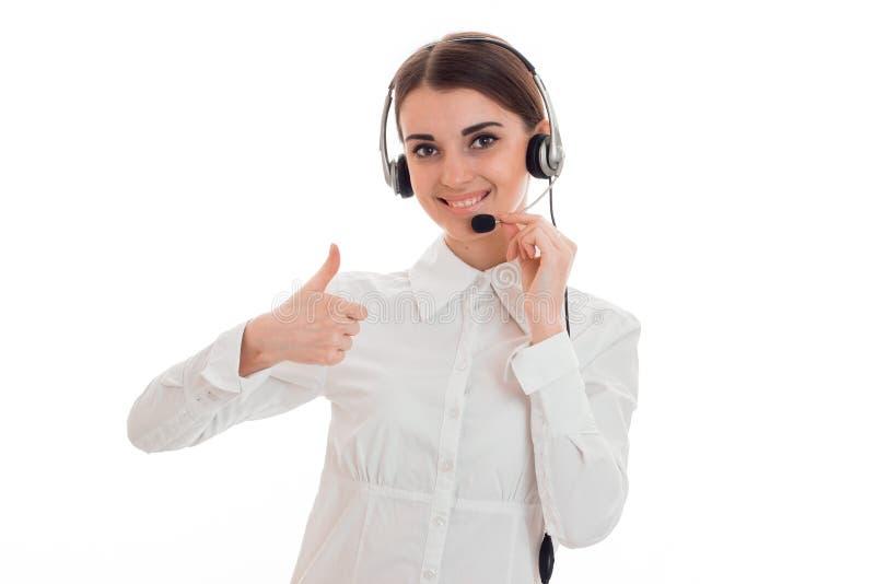 耳机的美丽的女孩和微笑在一件白色衬衣和展示类 库存照片