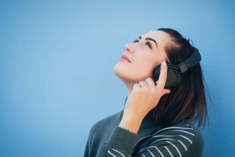 耳机的美丽的妇女在灰色礼服的蓝色墙壁背景,查寻 免版税图库摄影