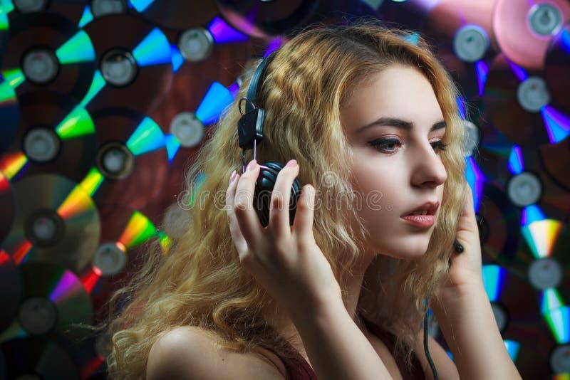 耳机的美丽的妇女获得乐趣并且听音乐 库存图片