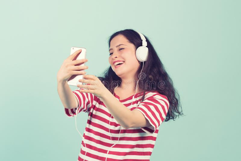 耳机的美丽的少妇听到音乐和唱歌在颜色背景的 库存照片