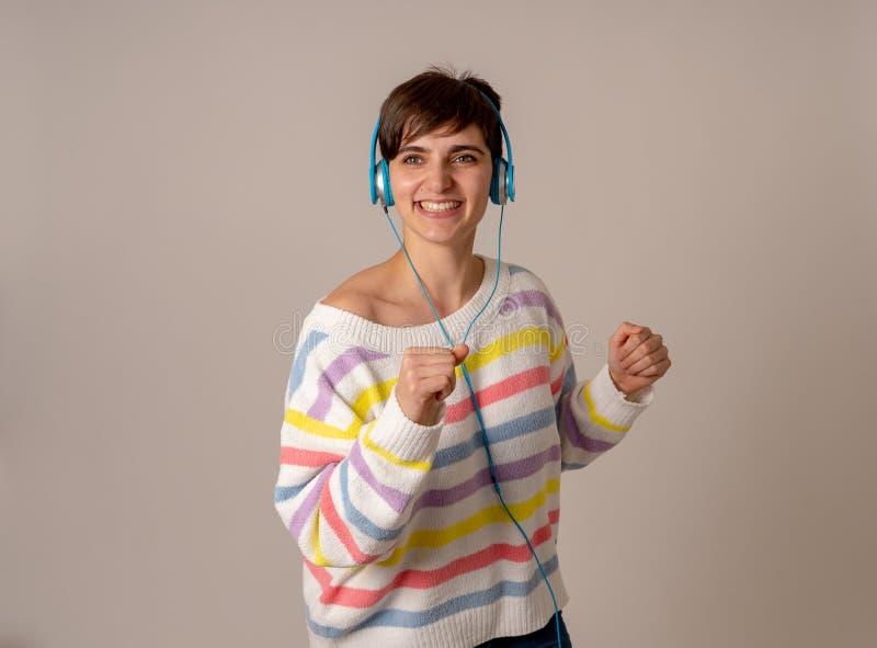 耳机的美丽的年轻女人听音乐和跳舞的隔绝在灰色背景 库存照片