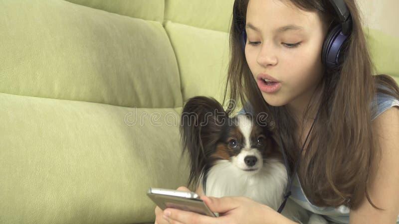 耳机的美丽的青少年的女孩唱在智能手机的卡拉OK演唱歌曲有狗的 库存图片