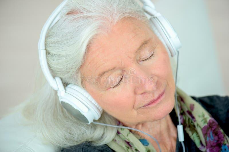 耳机的资深妇女 库存照片
