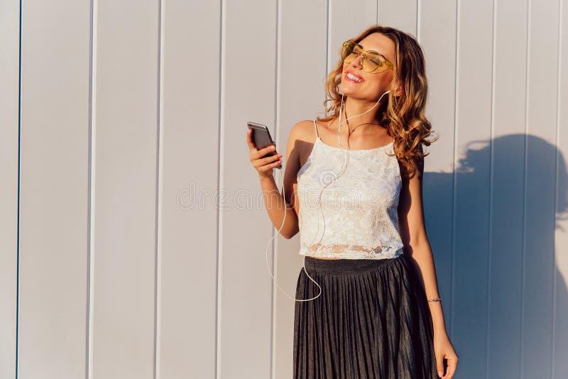 耳机的迷人的女孩听到在智能手机的音乐的 免版税图库摄影
