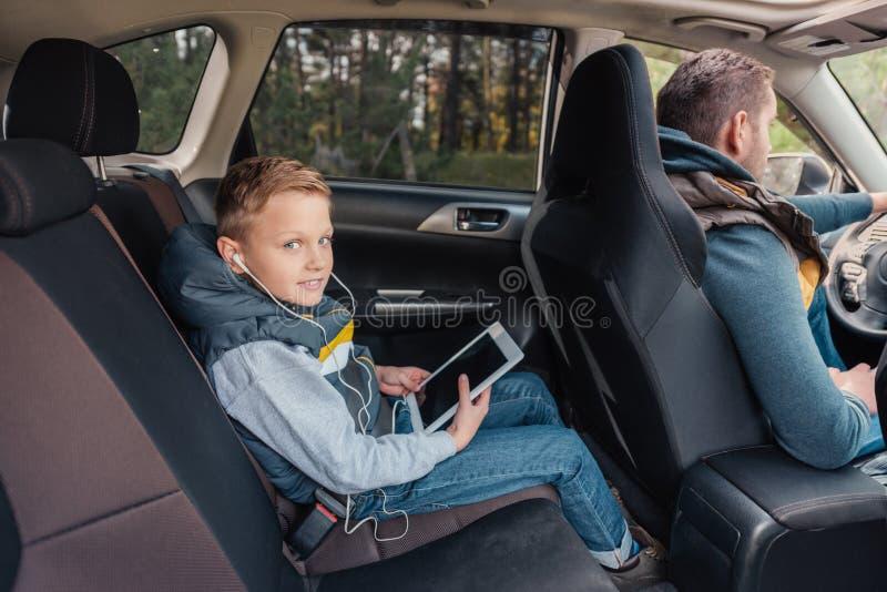 耳机的逗人喜爱的小男孩使用数字式片剂和看照相机,当坐与父亲时 库存照片