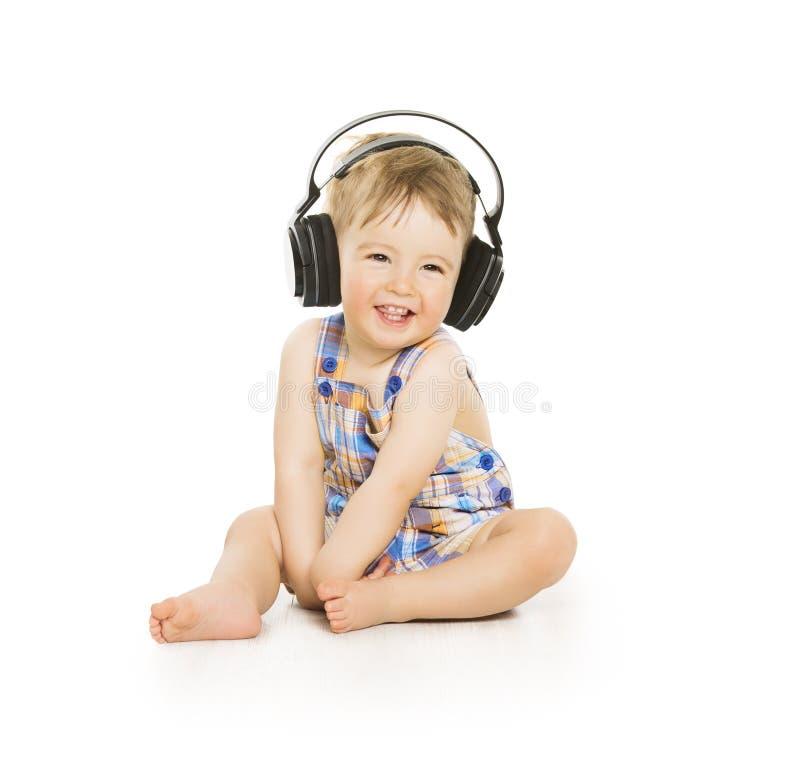 耳机的婴孩听到音乐,小孩子的被隔绝  免版税库存照片