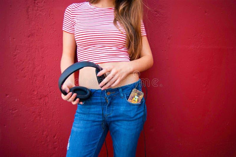 耳机的年轻美丽的女孩听到音乐的 免版税库存照片