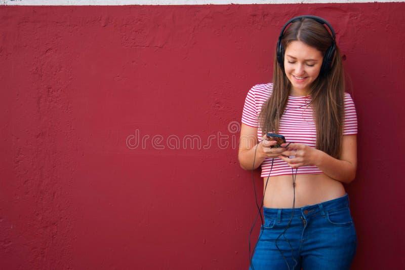 耳机的年轻美丽的女孩听到音乐的 免版税库存图片