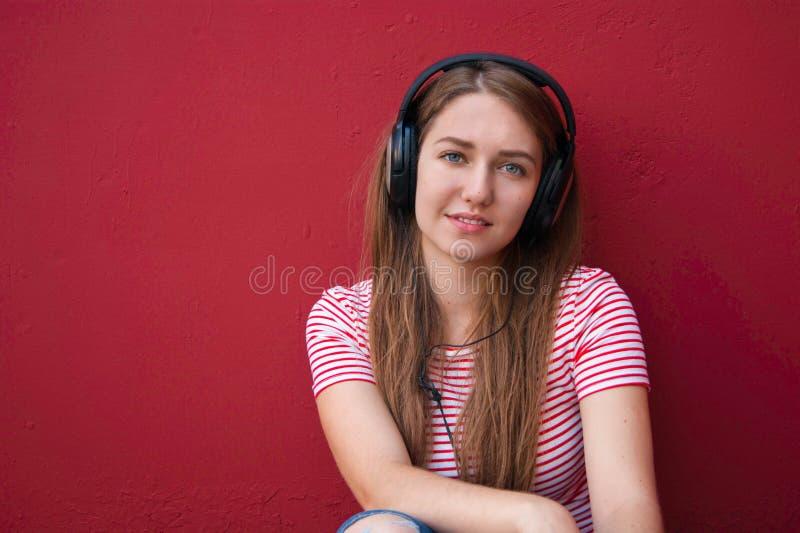 耳机的年轻美丽的女孩听到音乐的 库存图片