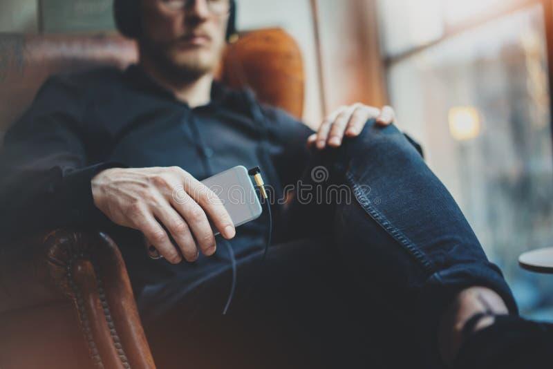 耳机的画象英俊的有胡子的人听到音乐的通过手机在现代顶楼 坐在葡萄酒的人 库存图片