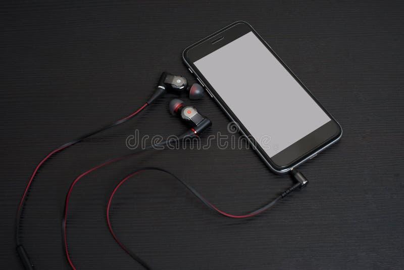 耳机连接到手机 免版税库存图片
