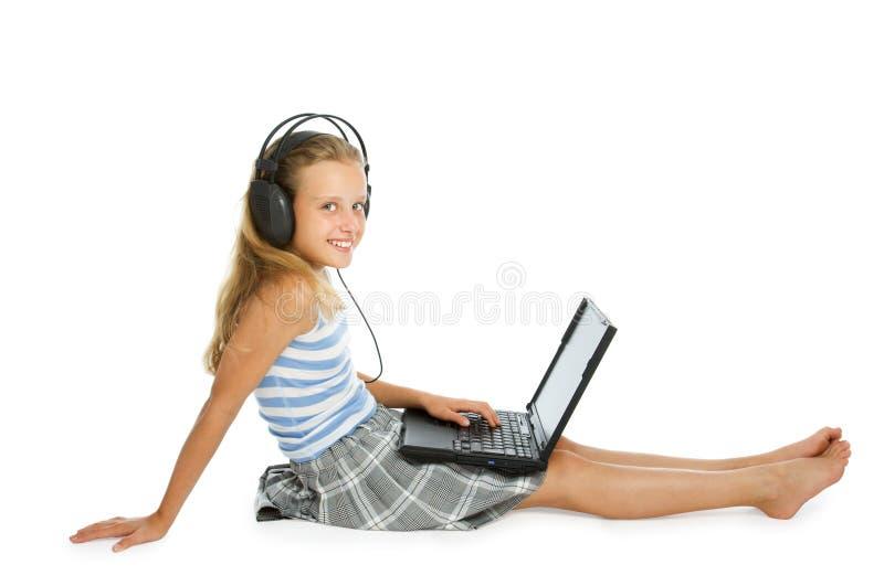 耳机青少年女孩的膝上型计算机 库存图片