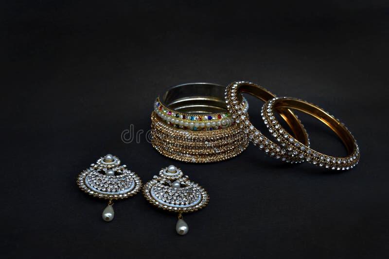 耳环和手镯有银色和馏金的 库存图片
