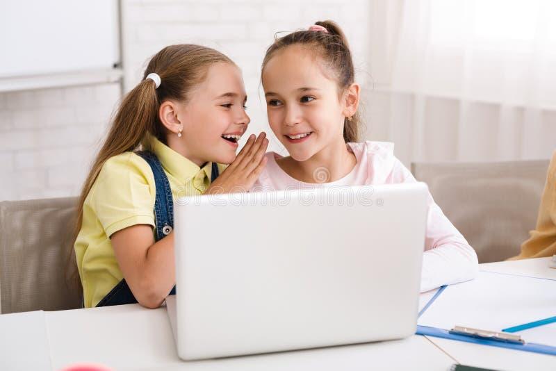 耳语和使用膝上型计算机的同学在教训以后 库存图片