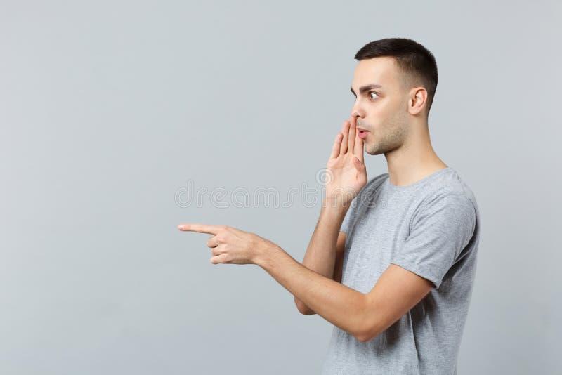 耳语惊奇的年轻人侧视图便服的在他的手后的秘密指向在旁边被隔绝的食指 免版税库存照片
