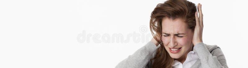 耳鸣的病的少妇或听到大声的音乐 免版税图库摄影