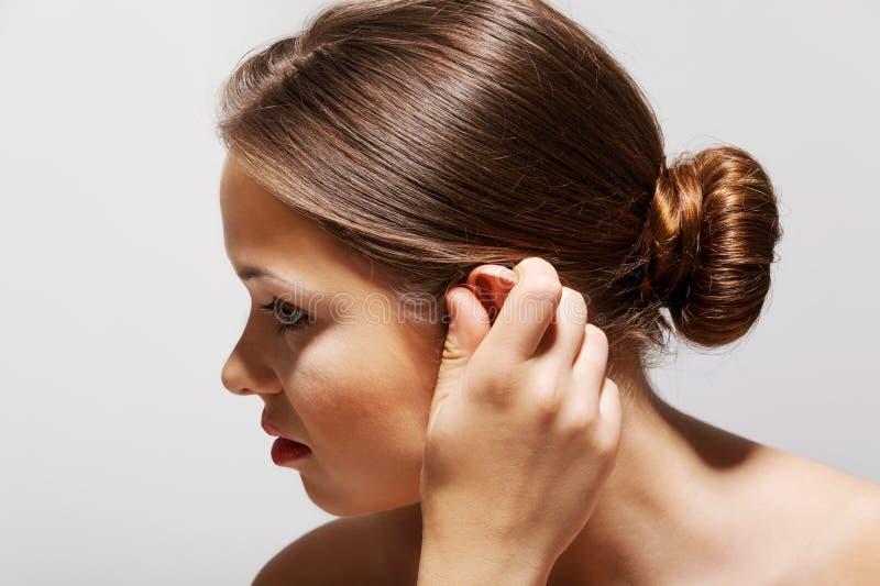 耳鸣 旁边外形病女性特写镜头有接触她痛苦的头的耳痛隔绝在蓝色背景 库存照片