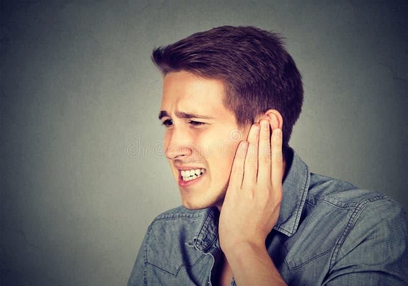 耳鸣 有病的人接触他痛苦的头的耳痛 库存图片